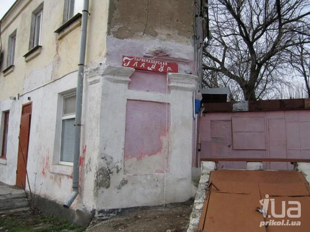 Вывеска парикмахерской «Гламур» на ободранной стене дома